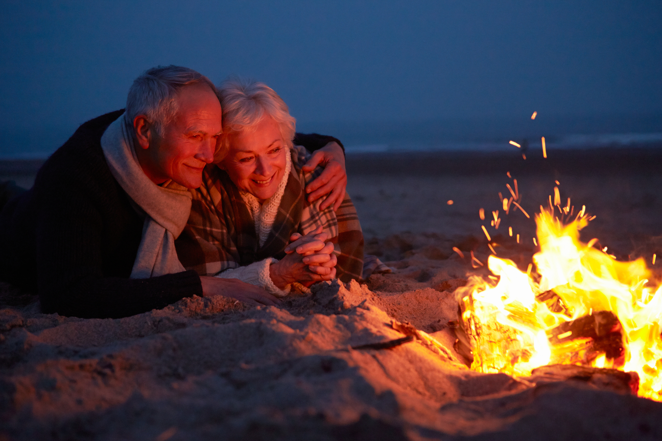 Senior couple sitting by the fire on the beach
